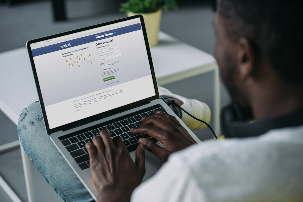 man sitting at a computer showing the Facebook login screen