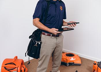 technician holding technology for restoration work
